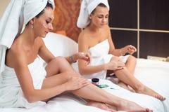 De vrouwen die op een bed zitten die vochtinbrengende crème toepassen romen benen af Stock Foto