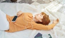De vrouwen die oranje overhemden dragen luisteren aan muziek en zijn gelukkig stock foto