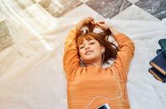 De vrouwen die oranje overhemden dragen luisteren aan muziek en zijn gelukkig stock foto's