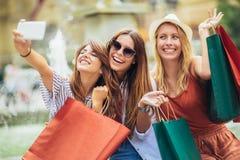 De vrouwen die samen en maken selfie foto winkelen stock foto
