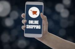 De vrouwen die smartphone in handen houden met voegen aan karproduct toe aan aankoop online op blauwe bokehachtergrond, met onlin stock afbeeldingen