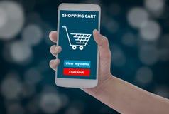 De vrouwen die smartphone in handen houden met voegen aan karproduct toe aan aankoop online op blauwe bokehachtergrond, met onlin stock afbeelding