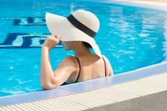De vrouwen die strohoeden dragen en ontspannen in het zwembad royalty-vrije stock foto