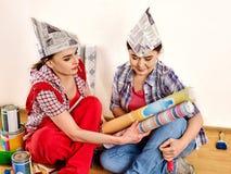 De vrouwen die van het reparatiehuis Bank met verf voor behang houden Stock Afbeeldingen