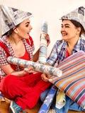 De vrouwen die van het reparatiehuis Bank met verf voor behang houden Royalty-vrije Stock Afbeeldingen
