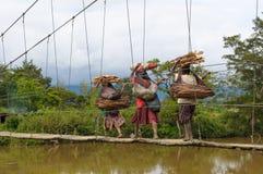 De vrouwen die van Papuan brug, Wamena, Papoea kruisen Stock Foto