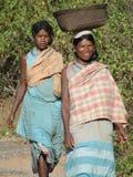 De vrouwen dragen goederen op hun hoofden Royalty-vrije Stock Afbeeldingen