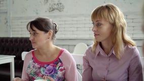 De vrouwen drinken thee in een koffie De collega's in een koffie voor een kop thee bespreken het werkplan stock videobeelden