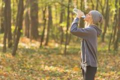 De vrouwen drinkwater van de geschiktheidsagent in het park stock foto