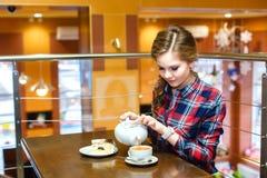 De vrouwen in een plaidoverhemd giet groene thee Stock Fotografie