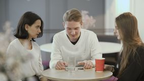 De vrouwen en de man zitten in café op het werk stock video