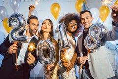 De vrouwen en de mannen die van partijmensen nieuwe jarenvooravond 2018 vieren Royalty-vrije Stock Afbeelding