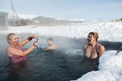 De vrouwen fotografeerden terwijl het zwemmen in geothermisch kuuroord in de hete lente Royalty-vrije Stock Foto's
