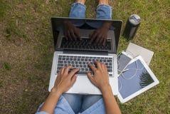 De vrouwen gebruiken laptops in de tuin stock fotografie