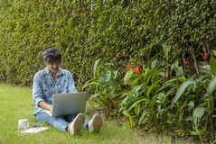 De vrouwen gebruiken laptops in de tuin stock foto