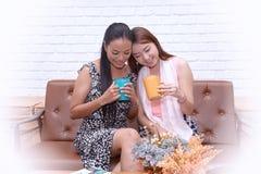 De vrouwen genieten van een drank, luisteren aan muziek en bespreking in de woonkamer stock foto