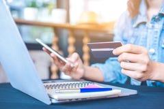 De vrouwen houden creditcards en gebruiks mobiele telefoons aan online het winkelen stock afbeelding