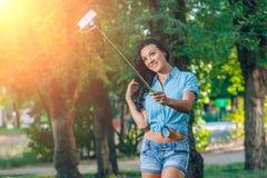 De vrouwen houden monopod gebruik de slimme telefoon foto neemt Royalty-vrije Stock Fotografie