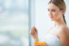 De vrouwen houden oranje paraffinekom Vrouw in schoonheidssalon royalty-vrije stock foto