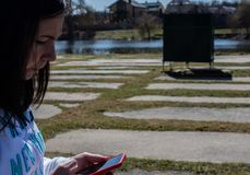De vrouwen houdt een telefoon tegen de achtergrond van de rivier Stock Afbeeldingen