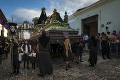 De vrouwen kleedden zich in zwart dragend een reuzevlotter in een straat van de oude stad van Antigua tijdens een optocht van de  Royalty-vrije Stock Afbeeldingen