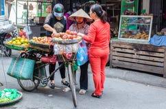 De vrouwen kunnen gezien het kopen vruchten van de straatventer van hun fiets in het Oude Kwart van Hanoi Stock Foto's