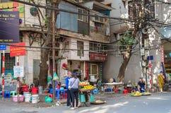 De vrouwen kunnen gezien het kopen vruchten van de straatventer van hun fiets in het Oude Kwart van Hanoi Royalty-vrije Stock Foto