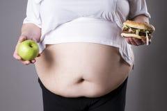 De vrouwen lijden aan zwaarlijvigheid met grote hamburger en appel in handen Het concept van de ongezonde kost Gefrituurde kip of Royalty-vrije Stock Foto's
