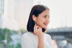 De vrouwen luisteren aan muziek van witte hoofdtelefoons En gebruikend handenaanraking om diverse functies, gelukkige stemming te royalty-vrije stock foto's