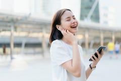 De vrouwen luisteren aan muziek van witte hoofdtelefoons En gebruikend handenaanraking om diverse functies te gebruiken royalty-vrije stock foto