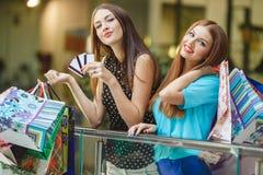 De vrouwen maken aankopen met creditcards bij de wandelgalerij Royalty-vrije Stock Afbeeldingen