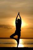 De vrouwen mediteren op zonsondergang Stock Foto's