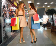 De vrouwen met het winkelen zakken doen aankoop bij winkel royalty-vrije stock afbeeldingen