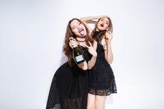 De vrouwen in nacht kleden het drinken champagne en het tonen tonque Stock Fotografie