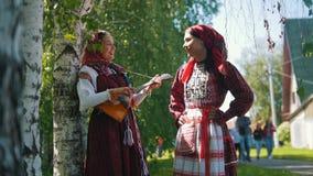 De vrouwen in nationale Russische kostuums bevinden zich dichtbij berk één van hen spelen de balalaika stock video