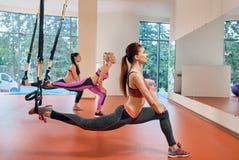 De vrouwen oefenen met trx uit stock foto's