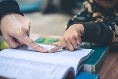 De vrouwen onderwijzen kinderen om boeken te lezen in hun vrije tijd in een stil milieu royalty-vrije stock afbeeldingen