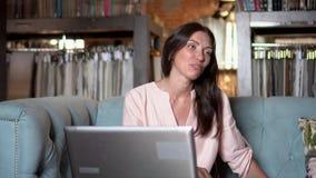 De vrouwen op een bank bespreken textielsteekproeven Het jonge meisje spreekt aan de cliënt betreffende samenwerking stock videobeelden