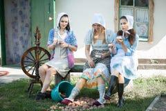 De vrouwen op de portiek drinken thee en bespreking Rustieke retro stijl royalty-vrije stock afbeeldingen
