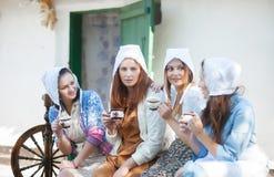 De vrouwen op de portiek drinken thee en bespreking Rustieke retro stijl royalty-vrije stock foto's