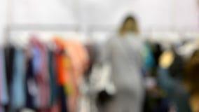 De vrouwen in de opslag kiezen kleren stock video