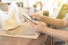 De vrouwen overhandigen het gebruiken van telefoon op vaatwerk in restaurant Royalty-vrije Stock Fotografie