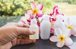 De vrouwen overhandigen het nemen van kleine fles van kuuroordshampoo of douchegel met Royalty-vrije Stock Foto's