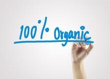 De vrouwen overhandigen het schrijven van 100% Organisch op grijze achtergrond voor zaken Stock Afbeelding
