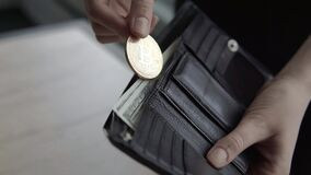 De vrouwen overhandigen het zetten van een gouden gouden bitcoinmuntstuk in zijn portefeuille Cryptocurrency wereldwijd en digita stock videobeelden