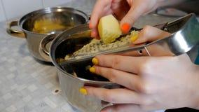 De vrouwen overhandigt de kokoneffenheden de aardappel op een rasp stock footage