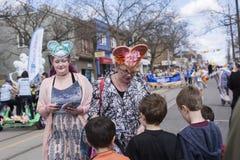 De vrouwen in Pasen-kostuum verdelen giften aan kinderen langs de Koningin Street East in de Parade 2017 van Strandenpasen Stock Foto's