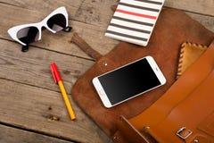 de vrouwen plaatsen met zak, slimme telefoon, zonnebril, blocnote, pen en beurs op bruin houten bureau royalty-vrije stock fotografie