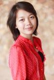 De vrouwen in rood overhemd met glimlach zien onder ogen Royalty-vrije Stock Fotografie