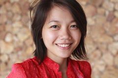 De vrouwen in rood overhemd met glimlach zien onder ogen Royalty-vrije Stock Foto's